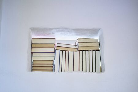 Bright and sunny detail of stack of books in a space in a textured white wall, copy space and low angle