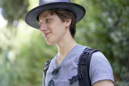 Young handsome man with a hat happily smiling in his summer holidays outside in beautiful greenery Stok Fotoğraf