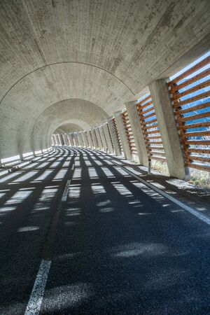 tunnel in the alps built of concrete with one side shut with wooden planks creating beautiful light stripes on the ground