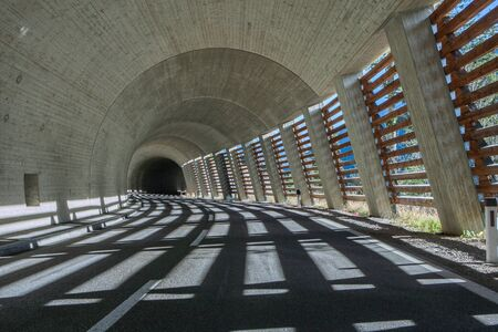 Dynamic road tunnel with a winding road in the Alps and beautiful lighting
