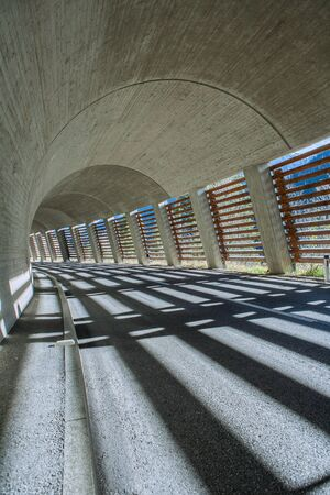 Dynamic angle of a round tunnel in the alps built of concrete with one side shut with wooden planks creating beautiful light stripes on the ground