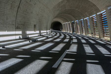 tunnel with black asphalt and winding road in the Alps in beautiful light Stok Fotoğraf