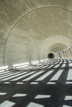 light concrete tunnel with black asphalt and serpentine road in the alps with beautiful streaks of light on the ground Stok Fotoğraf