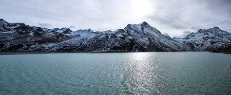 panorama shot in the alps in autumn with snowy mountains in the background and water of the silvretta dam in the foreground