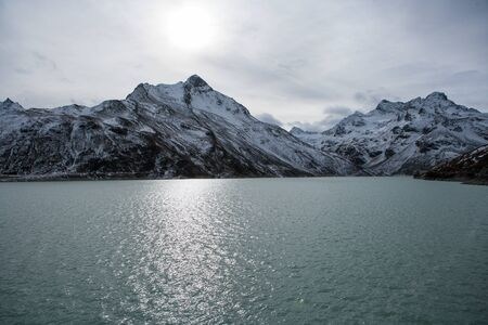 Water of a mountain lake with snowy hilltops in the background in evening light Stok Fotoğraf