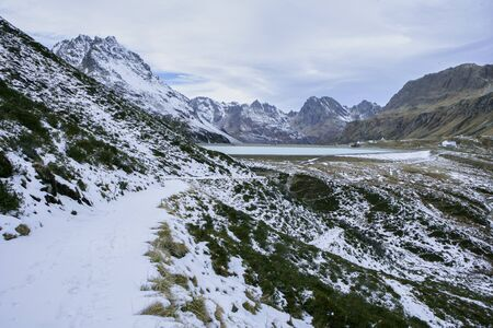 small hiking trail in the mountains with snow on the silvretta mountains with a view of the dam