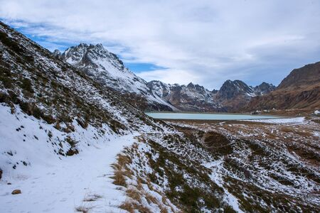 hiking trail in the mountains with snow, silvretta in austria with a view of the dam