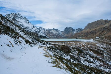 Mountain path in the mountains and snow with a view of the Silvretta dam in Austria Stok Fotoğraf