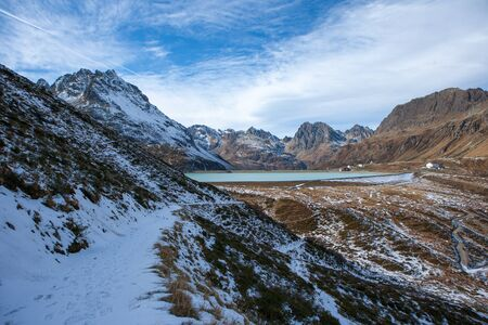 Mountain path with snow with a view of the Silvretta dam in Austria near the Italian border