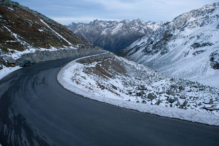 black asphalt with serpentines and snow in the ötztal mountains in austria from a higher perspective