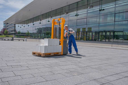 man in overalls operates an electric stacker loaded with boxes Stok Fotoğraf