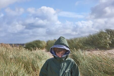Boy in sand dunes in Denmark, hiding his face in green jacket to protect himself from the cold north wind while looking around, in the background a northern area