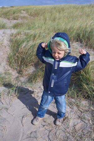 Little blond boy in blue windcheater, tensioning his arms happy, for fighting against the North Wind in sand dunes in Scandinavia