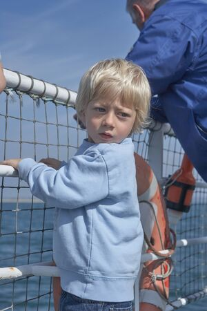 Blond Small child clinging to the railing on ferry, looking back for taking a look, in the background a beautiful blue sea