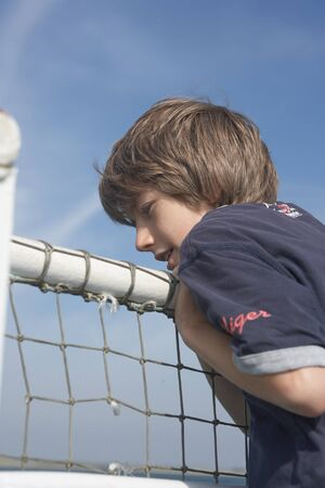 Brown-haired boy in t-shirt, hanging over the railing of a ferry and looking around, in the background a little rainbow