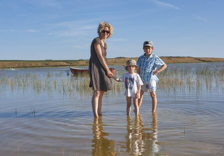 Blond beautiful mother with her two kids, standing in a lake with aquatic plants and a boat, in the background a green landscape Stok Fotoğraf