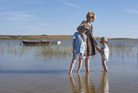 Blond mother with sunglasses, holding the sands of her son while keeping the other one in her arm, walking around in a lake with reed and boats, in Scandinavia Stok Fotoğraf