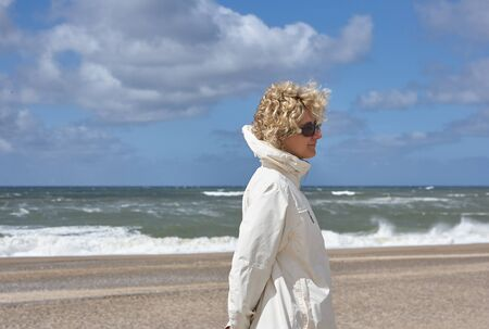 Blond woman with sunglasses, wearing a  windbreaker at the beach in Scandinavia, in the background the North Sea foaming with a lot of spray and a blue but cloudy sky