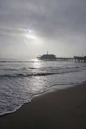Bright day at the beach of Santa Monica in California, sand and calm sea, in the background sunset and pier, bright sky