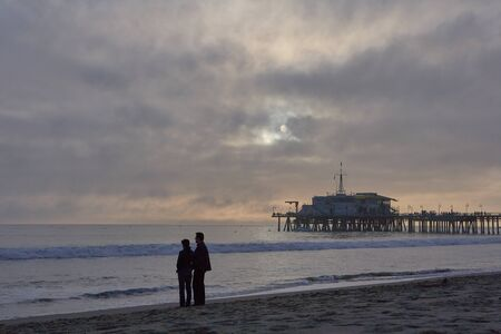 Very beautiful sunset in Santa Monica, a couple on the sand in the foreground, pier to the right, sea buoys and a cloudy sky in the background