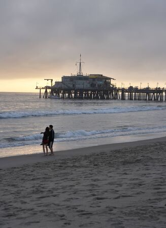 Santa Monica pier in the evening, a couple standing at the beach, the last rays of sunshine Stok Fotoğraf
