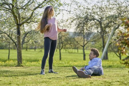 Young couple on a meadow between apple trees in spring laughing happily at each other and having fun