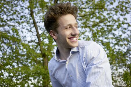 Portrait of a young handsome happily laughing man looking over his shoulder in beautiful greenery Stok Fotoğraf