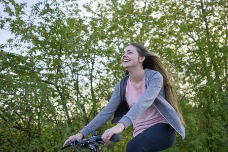 Young happily laughing woman with long hair riding a bike in beautiful greenery in springtime Stok Fotoğraf