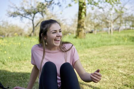 Young woman sitting in a meadow in spring laughing and having lots of fun in the background fruit trees
