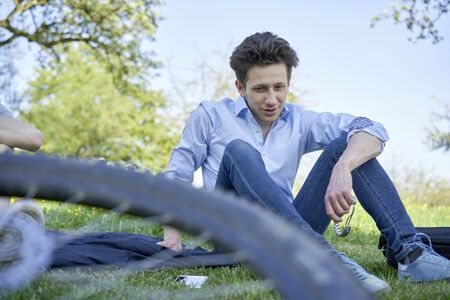 Young talking man sitting in a lawn during a bike tour in beautiful greenery Stok Fotoğraf