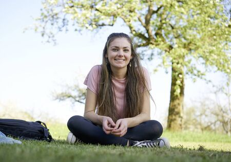 Smiling girl sitting on a meadow next to a backpack and a guy with sneakers, in the background a beautiful tree with green leaves