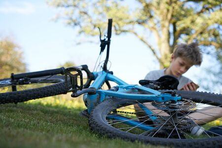 Boy hanging out on a meadow with his smartphone next to his blue bicycle, in the background a tree Stok Fotoğraf