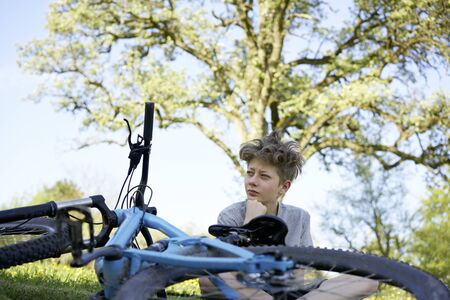 Handsome teenage boy having a break during a bike tour being in a pensive mood and sitting in a meadow with his bike in front of him, in the background a tree Stok Fotoğraf