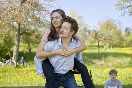 Young man carrying his girlfriend on his back while making duckface on a meadow in the nature, in the background a little blond boy, bicycles and trees
