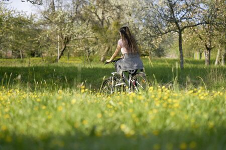 Woman on bicycle in a meadow with yellow flowers  and trees in beautiful nature, driving away Stok Fotoğraf