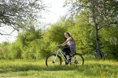 Smiling young woman on bicycle in a meadow with yellow flowers, in the background bushes and bicycles leaning on an apple tree