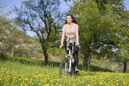 Young woman riding a bicycle in the nature on a meadow with yellow buttercups and trees, enjoying the sun