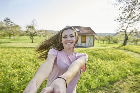 Young happy woman, dancing around in German countryside  in the background grasslands, trees and a half-timbered house