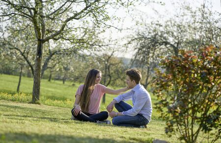 Young couple in german green landscape with trees and bushes, the girlfriend is stroking the boyfriend the cheek