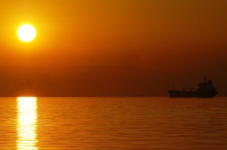 optimismo: Puesta de sol con un barco en el horizonte Foto de archivo