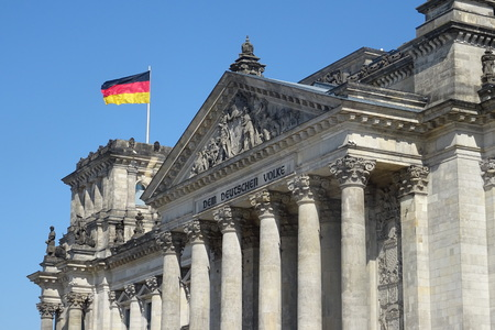 Exterior view of the historic building of Reichstag with a fluttering German flag