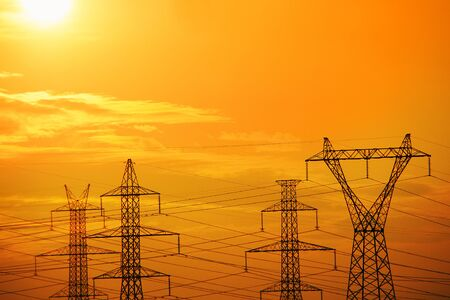 Silhouettes of electric pylons and power lines in sunset
