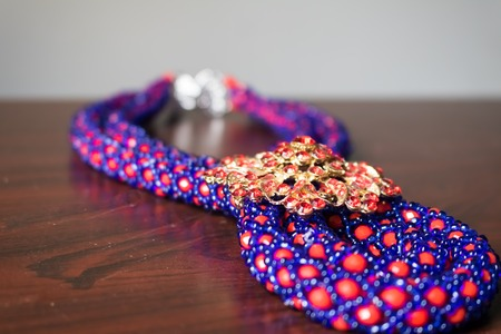 Handmade necklace made of red and blue beads with a brooch and clasp Banque d'images - 100348156