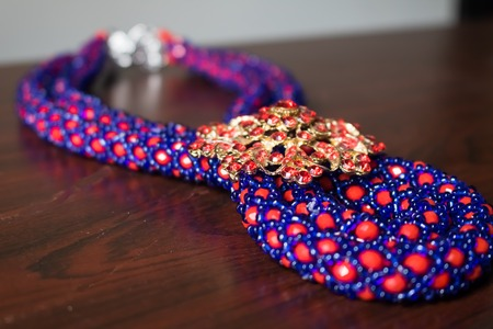 Handmade necklace made of red and blue beads with a brooch and clasp