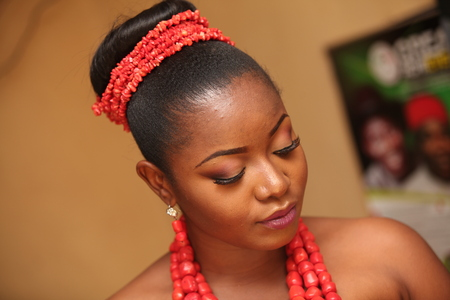 African bride dressed in her second attire and beads on her traditional wedding day