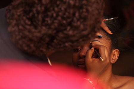 An African woman getting makeup from a beautician for her traditional wedding rites.