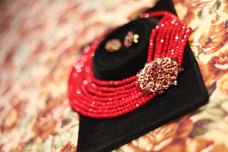 Handmade red necklace with glittering broach on a black velvet holder. Made for a bride in Nigeria, Africa for her traditional wedding
