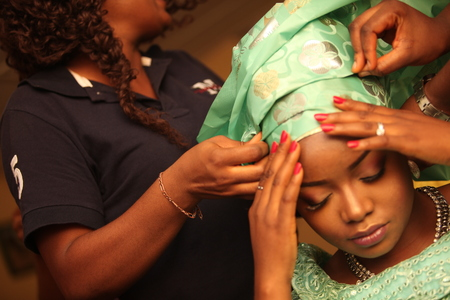 The bride gets her head gear fixed by beauticians on her traditional wedding day.