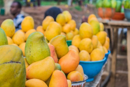 Yellow, red and green african mango fruits arranged in small portions for sale in a market. Stock fotó