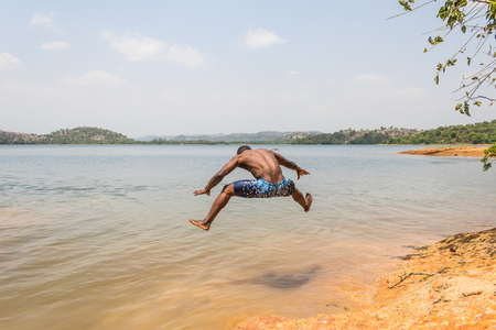 A young muscular athletic man takes a leap dive into the river in the morning.
